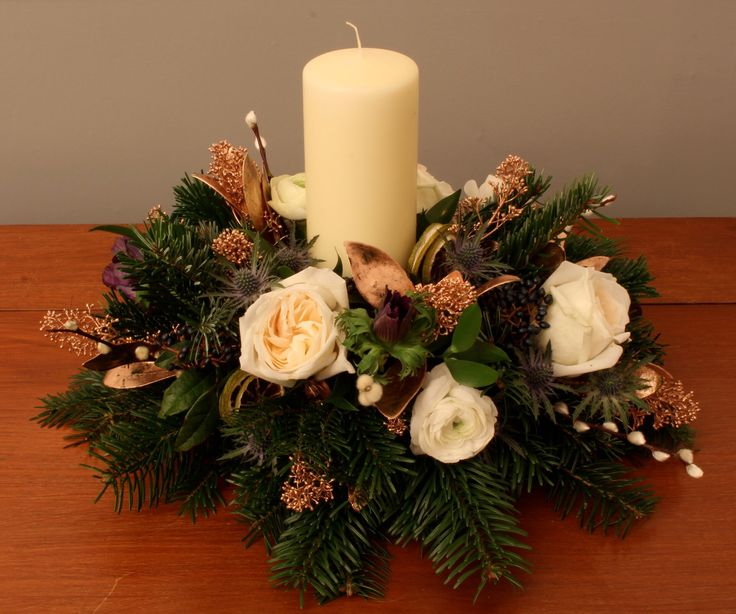 A luxurious table centrepiece with copper sprayed accent foliage, ranunculus and garden roses.
