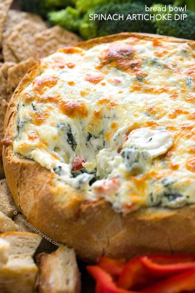 This rich and creamy Hot Spinach and Artichoke Dip recipe is easy, delicious and totally cheesy! Once mixed, this dip is baked until warm and melty in a bread bowl for the perfect football game appetizer.