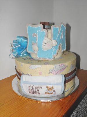 Torta di pannolini con accessori utili al neonato: coperta in pile per lettino, bavaglino per la pappa e nome in feltro per la cameretta del piccolo
