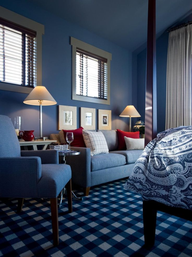 A houndstooth fabric presented in a shade of cobalt covers the room's classic loveseat. Framed photos, displayed at waist height, a potted boxwood and a porcelain, hand-painted urn lend visual interest.
