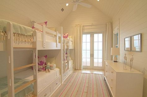 Sweet cottage girls' room features a vaulted ceiling and walls clad in shiplap lined with side by side built-in bunk beds with storage drawers dressed in white bedding and blue herringbone throw blankets facing a white 6 drawer dresser across from a striped rug.