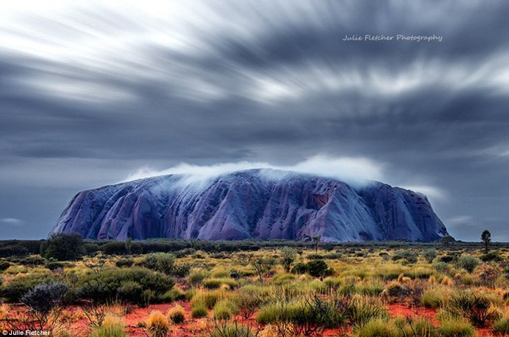 First Light: This image shows Uluru, usually a bright earth red colour, at first light in ...