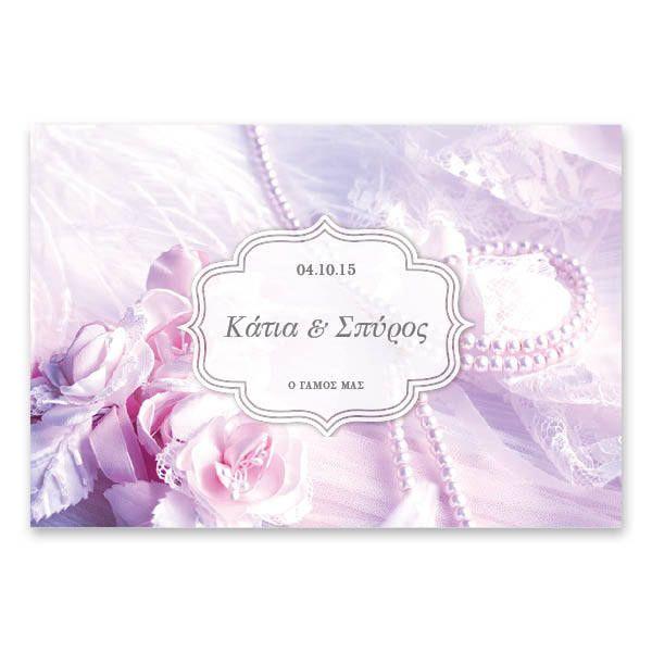 Ρομαντικές Λιλά Πέρλες | Πέρλες, υφασμάτινα λουλούδια και σατέν σε ροζ μπομπονιζέ τόνους συνθέτουν ένα ρομαντικό προσκλητήριο γάμου για να ανακοινώσουν τα χαρμόσυνα νέα. Εκτυπώνεται σε χαρτί της επιλογής σας, μεγέθους 15 x 22 εκατοστών, οριζόντιας διάταξης και συνοδεύεται από ασορτί φάκελο. Lovetale.gr