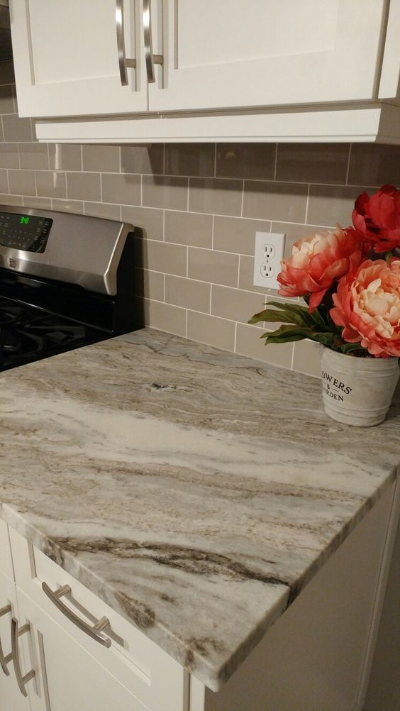 Fantasy Brown Granite Counters, Taupe Glass Tile Backsplash and White Shaker Cabinets.