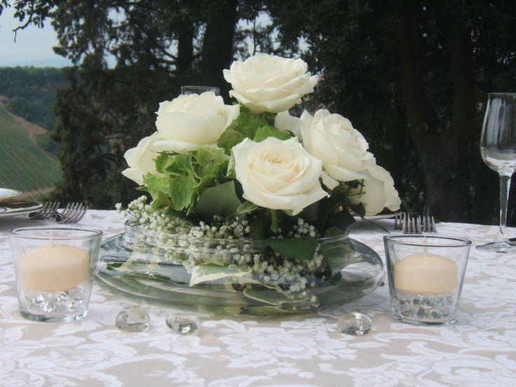 matrimonio: centrotavola con rose bianche in vaso di vetro, con decorazioni in vetro e candele