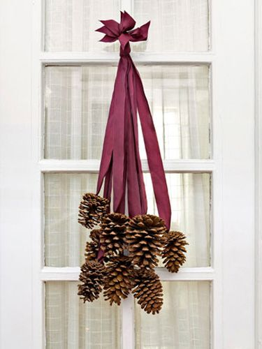Not all DIY front-door decor requires a foam wreath form. To make this elegant cluster, we selected 8 four- to six-inch pinecones and 8 two-foot-long pieces of silk ribbon. Use a hot-glue gun to adhere the last two inches of each ribbon to the base of a cone. After the glue dries, collect all the ribbon ends and stagger them so that the cones fall at varying lengths. Tie the ribbon ends together in a knot, trim the tips so they are uniform, and slip the knot over a finishing nail…