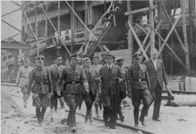 Reichsfuehrer SS Heinrich Himmler tours the Monowitz-Buna building site in the company of SS officers and IG Farben engineers. Among those pictured are: Rudolf Brandt (left, in SS uniform slightly behind Himmler), Heinrich Himmler, Max Faust (wearing the fedora) and the Auschwitz commandant Rudolf Höss (next to Faust). Faust, who was an IG Farben engineer, was the head of building operations at Monowitz-Buna.