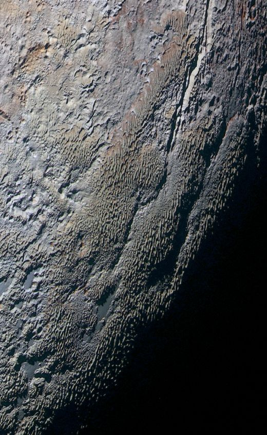 This color image of Pluto taken by NASA's New Horizons spacecraft shows rounded and bizarrely textured mountains, informally named the Tartarus Dorsa, that rise up along Pluto's terminator and show intricate but puzzling patterns of blue-gray ridges and reddish material in between. This view, roughly 330 miles (530 kilometers) across, combines blue, red and infrared images taken by the Ralph/Multispectral Visual Imaging Camera (MVIC) on July 14, 2015.
