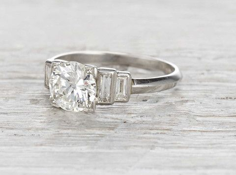 Antique Art Deco engagement ring made in platinum and centered with a 1.10 carat old European cut diamond. Accented with four baguette cut diamonds. Circa 1925.