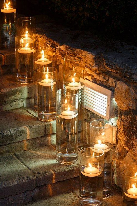 Single floating candles in narrow glass hurricanes illuminate stone steps for guests