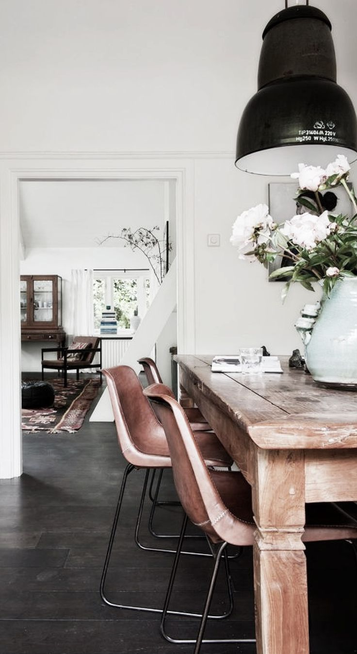 rustic wood dining table, dark floors, white walls and industrial lamp