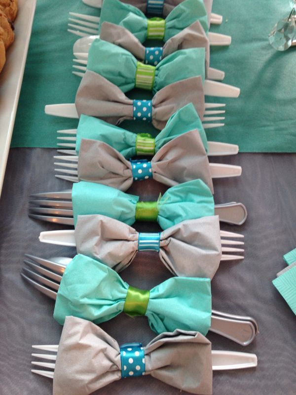 Use paper napkins and washi tape – or fabric and satin ribbon, depending on your budget. Wrap the napkin loosely around the cutlery. Wrap tight in center with tape/ribbon. Fluff edges to crea…