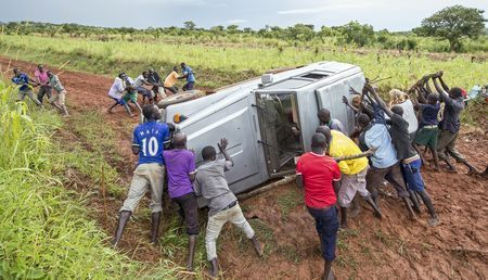Young men from the tiny Ugandan village of Pire team up to right a 4-wheel-drive vehicle after it rolled on its side in the notorious African mud during a rain. Two women passengers in the rollover join the effort and press against the roof. Utilizing para-cord and foraged wood for leverage, the vehicle was flipped upright, and the men were introduced to 'high-fives' by the celebrating women. Despite exterior damage, the truck started and the group continued on to Kidipo National Park...