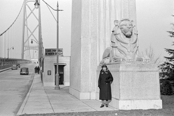 Two lane blacktop with no lines! A woman beside the lion sculpture at the entrance to the Lions Gate Bridge 1939 by James Crookall