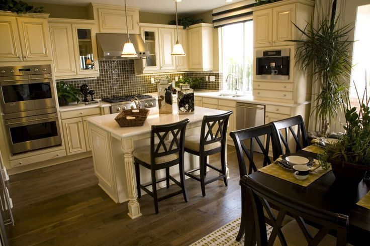 White kitchen with all-white island with seating for two plus separate dining table within the open kitchen and dining space.