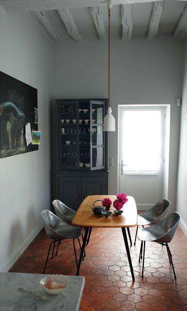 """""""Surowa"""" jadalnia. Na podłodze terakota w kolorze cegły, ułożona w plaster miodu. Reszta wnętrza w neutralnych szarościach."""