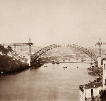 Ponte Pênsil, com a ponte Luís I em construção, em c.1885.    [Foto: Emílio Biel; Wikimedia Commons]