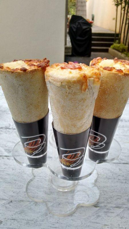 Pizza en forma de cono preparada y horneada en el lugar del evento,  Ingredientes como queso mozarella, gouda, chihuahua, jamón, pepperoni, albahaca, elotes...