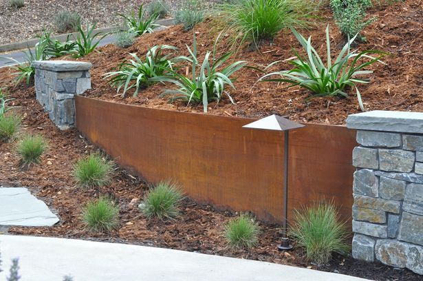 The Cor-Ten steel retaining walls follow the contour of the walkway. The weathering steel walls are interspersed with curving stone walls, w...
