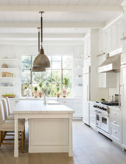 Elegant modern farmhouse kitchen in California by Giannetti Home/white cabinets/stainless appliances/vintage pendant lights/marble countertop/open wood shelving/steel windows/white oak wood floors/wood ceiling #traditionalkitchens #HomeAppliancesVintage