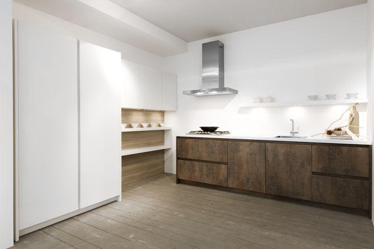 Prachtige open moderne keuken met een werkstation met houten keukenkasten en witte hoge kolomkasten aan de muur.