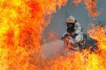 Pompier de l'U.S. Air Force en train de s'entraîner avec une tenue aluminée autonome, équipement de protection individuelle spécialement adapté aux feux d'hydrocarbures.