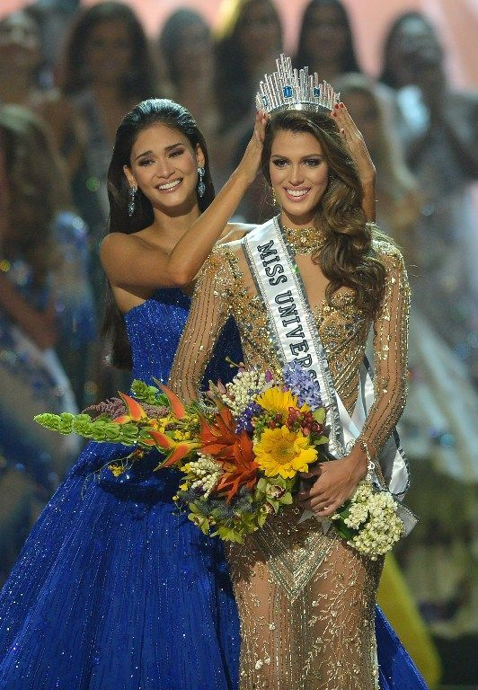 Miss Universe contestant Iris Mittenaere, right, of France is crowned the 2017 winner by former Miss Universe Pia Wurtzbach of the Philippines during the Miss Universe pageant at the Mall of Asia Arena in Manila on Jan. 30, 2017. Follow rickysturn/amazing women
