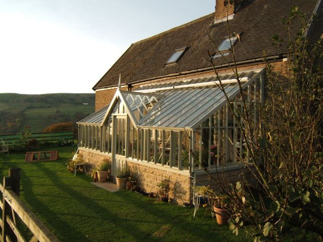 A monopitch greenhouse with a flat fronted lobby attached to the side of the house