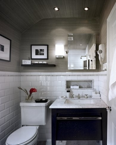 The texture on the walls, the pot lights, the black and white photos, practical yet minimal shelving above the toilet... love this.