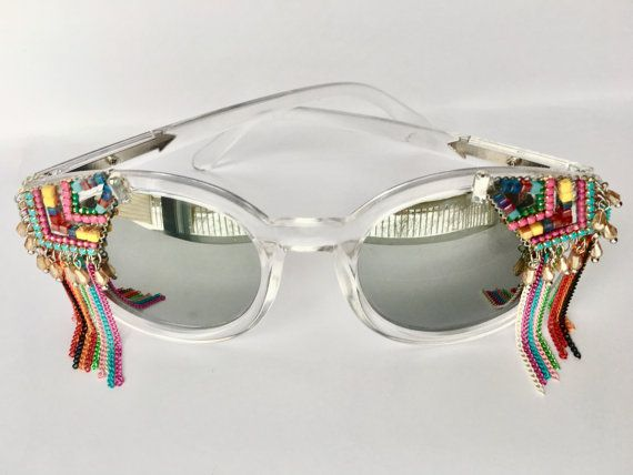Beautiful Pair of Transparent frame sunnies with silver reflective lenses, embellished with gorgeous beaded and fringed jewellery. One of a kind and handmade.  You may find Minor flaws, ships with a beautiful pouch to protect your sunnies.  Adhered with industrial strength glue.