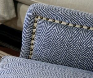 Twill tape with furniture tacks over it to disguise seam....Blue herringbone fabric and nailhead detail.