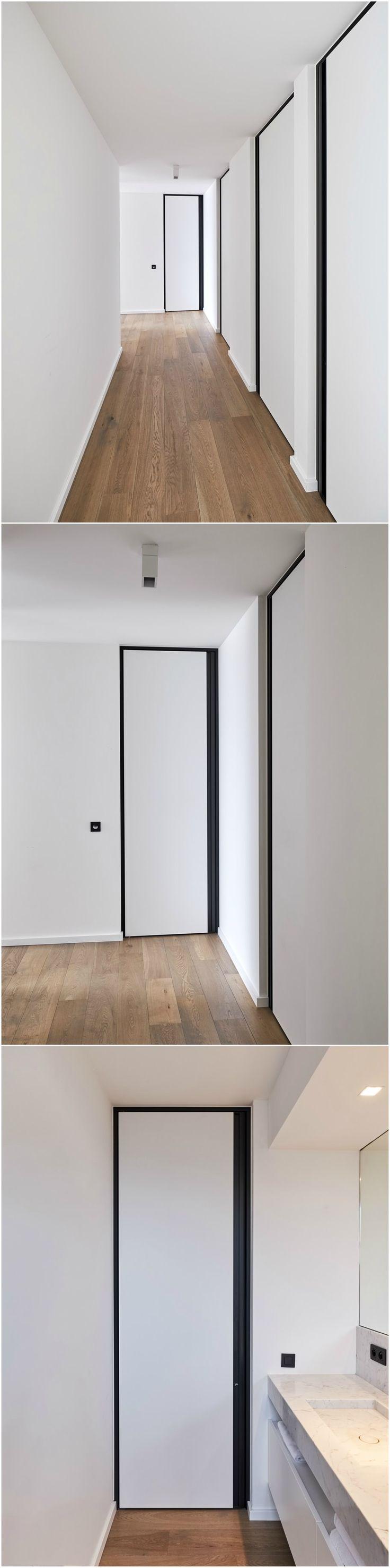 Recente realisatie waar witte binnendeuren van vloer tot plafond geplaatst werden in combinatie met een zwarte omlijsting en verticale handgreep. De zwarte accenten leveren een mooi contrast met de witte muren en houten vloer.