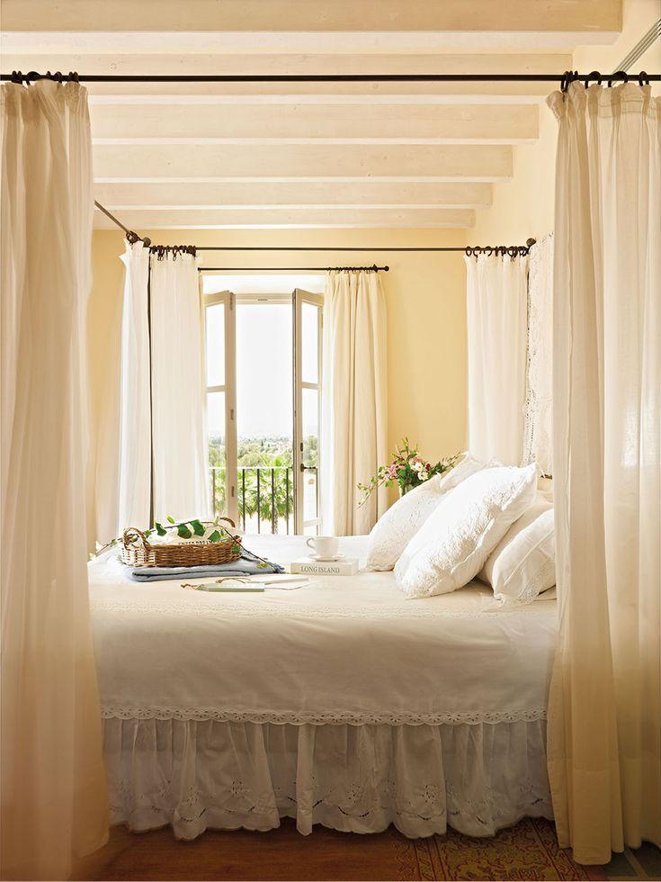 Cama con dosel y ropa de cama blanca junto a un balcón al jardín_00328914