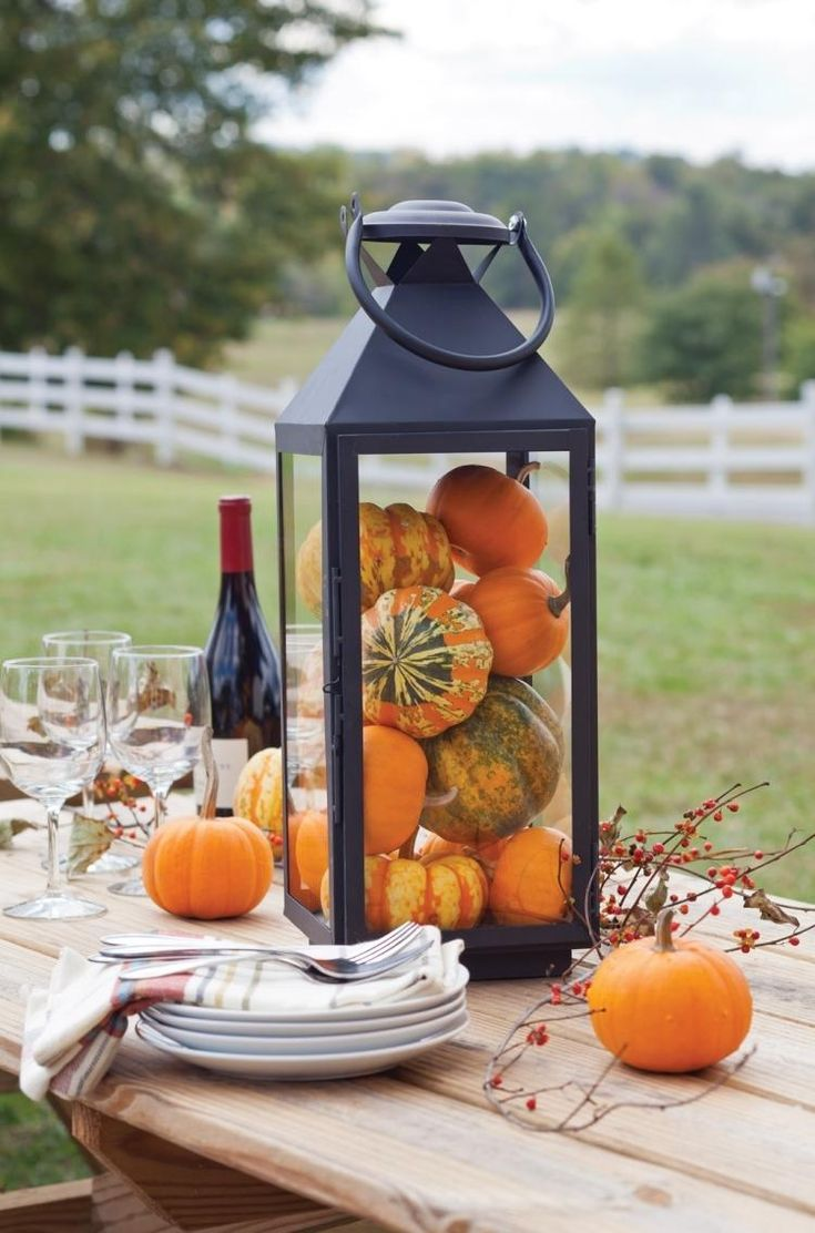 Small decorative pumpkins as table decoration in huge candle lantern