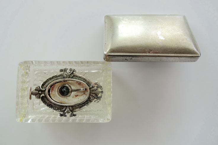 <The Left Eye of NeFeR-T-iTi(/Horus/Udjat)> 10/20/2015     by Masahide Kobayashi  2.7 (H.) × 7.4 (w.) × 4.8 (D.) cm Mixed Media : Vintage Soapbox Dish (Clear Pressed Glass with Rising Sun Relief) with Overlapping Lid (Anodized Aluminum Pressed Sheet) ; A Piece around the Aperture of Spiral Shell ; Eyeball-shaped Pendant Head by Nobumi Hasegawa (Hematite, Silver) ; Mirror/Frame-shaped Miniature Photo Stand (Silver) ; Clear Gel Wax for Aromatic Candle (Liquid Paraffin)