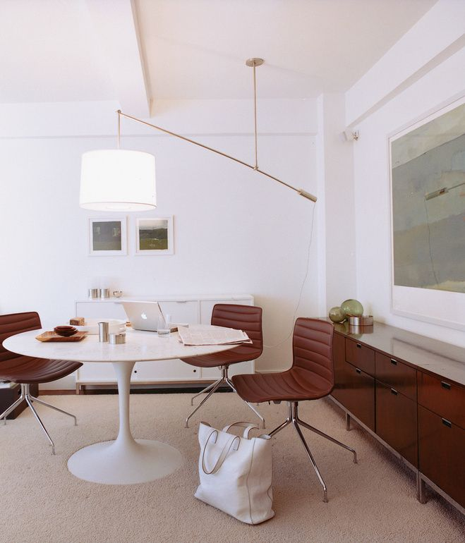 One of Goolrick's custom lights cantilevers over a marble-topped Saarinen Tulip table with the slight camber of a laden fishing pole.