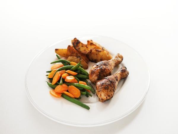 Verwarm de oven voor op 200 graden.Doe de kipdrumsticks in de braadzak. Voeg de braadstoomkruiden, de aardappel, de knoflook, het takje rozemarijn en de olijfolie toe. Sluit de zak af en schud deze voorzichtig. Doe de zak 1 uur in de oven.
