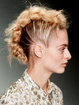 Attention, coiffure originale en vue ! Sur le défilé Simone Rocha, la tresse est fixée pour créer une crête rock et élégante à la fois. Une idée qui convient parfaitement aux chevelures blondes dont les reflets seront mis en valeur.