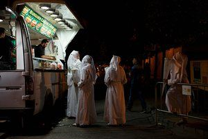 Penitents from the San Gonzalo brotherhood buy food at a mobile street food van after a 12 hour procession outside their church in Seville, Spain.