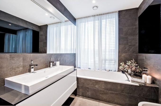 Koupelna přiléhající k hlavní ložnici je obložena zajímavě řezanou velkoformátovou dlažbou imitující kámen. Je zde vana a dvojumyvadlo Laufen osazené bateriemi Axor