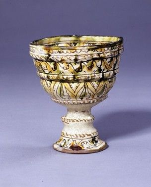 cup Museum number 1895,0810.1 Description Cup; earthenware; incised stylised design; interior with interlaced centrepiece surrounded by four birds, double spiral border; exterior with stylised foliate scroll bands of decoration; ridged foot; splashes of yellow, brown and green glaze. Date 14thC-15thC Made in: Cyprus (?) Found/Acquired: Cyprus, church (Byzantine) (Europe,Cyprus) Dimensions Height: 12.4 centimetres Diameter: 10.3 centimetres (rim) Registration number 1895,0810.1