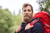 Smiling man with beard and backpack hiking Stock Image