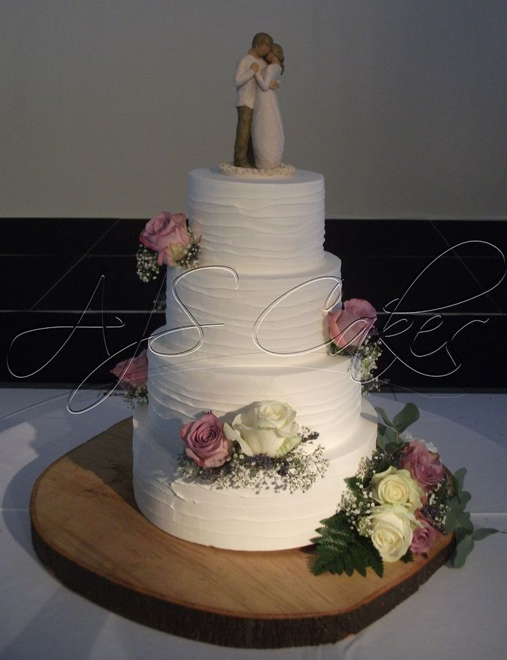 A four tier rustic style wedding cake with fresh flowers, set on a log slice.