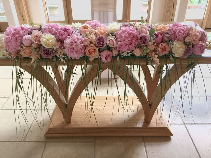 Top table arrangement at Rivervale Barn using pink and peach flowers with trailing grasses by www.tarniawilliams.co.uk