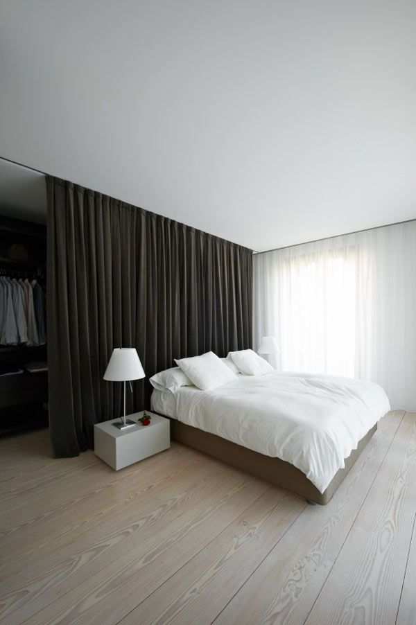 Minimalist. Wardrobe behind curtain for a room with no closet.