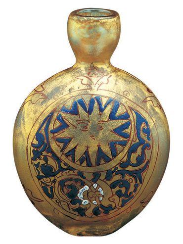 Paşabahçe Yassı Tılsım Parfüm Şişesi Mineli cam koleksiyonu-El Yapımı cam Şişe üzerine bir madalyon içinde insan yüzü gibi çizilmiş Güneş ve onu tamamlayan bir Hilal resmedilmiştir.Hilal figürünün içi ise,ejderhaları çağrıştıran bitkisel motiflerle süslenmiştir.Örneğine sık rastlanmayan Hilal,Güneş ve ejderha figürlerinin bir arada kullanılması şişenin orijinalinin tılsımlı olduğunu simgelemektedir.