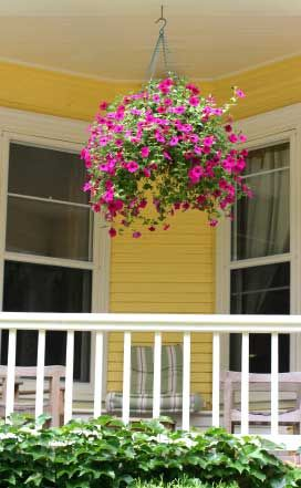 Colorful hanging basket on bright yellow porch