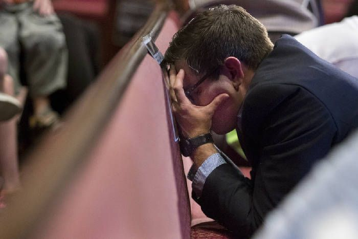 Chad Harris puts his face against a pew as he prays during a prayer vigil at Redemption Point Church on Thursday, July 16, 2015, in Chattanooga, Tenn. The vigil followed a shooting at both the Lee Highway Armed Forces Career Center and the Naval Operational Support Center on Amnicola Highway which left five dead, including the shooter, and a Chattanooga police officer wounded. Photo by Doug Strickland /Times Free Press.