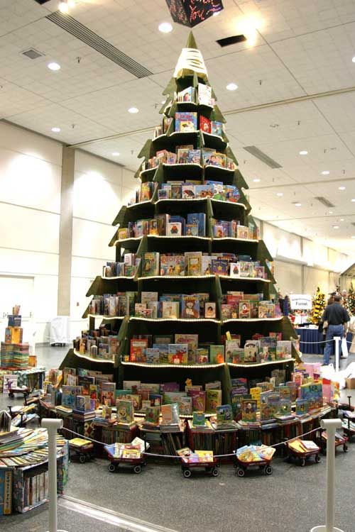 Book tree surrounded by red wagons filled with books. Lovely display.: