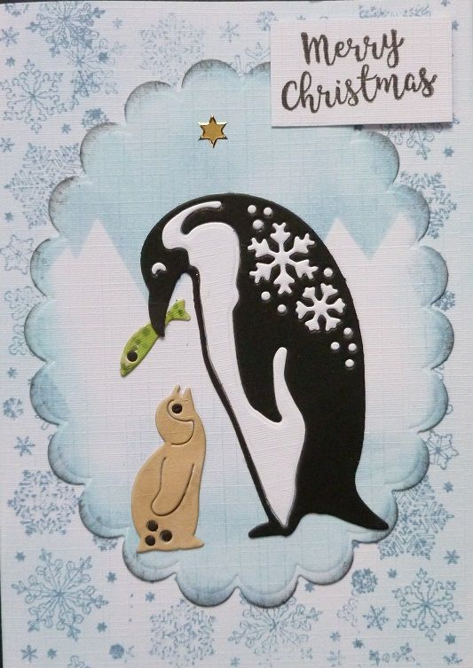 'P P Pick up a Penguin for Christmas' card. - Oval die by Spellbinder's.  Silver star peel off.  Black ink pad.  Tan, Green & Blue Promarker alcohol pens.  Rollagraph holder & snowflakes stamp.  Tumbled glass & Black soot Distress Inks.  Penguin dies and Merry Christmas stamp - free with Craft magazine.  December 2017.  Designed by Jennifer Johnston.